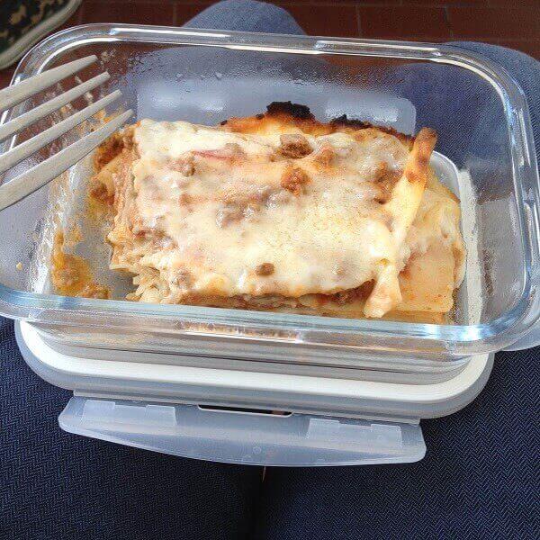contenitore in vetro con una porzione di lasagne fatte in casa